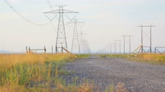 Powerlines and dirt road low shot Stock Footage