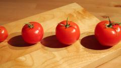 A row of tomatoes aligned by size Stock Footage