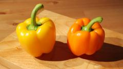 Two sweet peppers on a board Stock Footage