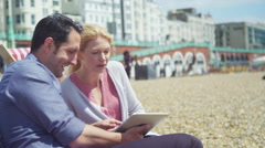 4K Couple on beach with computer tablet laughing at what they see on the screen Stock Footage