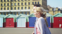 Happy romantic couple share a kiss as they walk past colourful beach huts Stock Footage