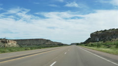 POV-Driving US 550 north in New Mexico morning with empty road past rocky mesas Stock Footage