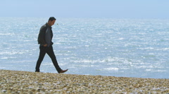 Attractive man walking on the beach, looking out to sea & skimming stones Stock Footage