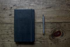 Black Leather Bound Notebook with Silver Pen Stock Photos