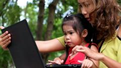 An asian girl and mother are using notebook computer at the park - stock footage