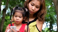 An asian girl and mother are playing funny game on smart phone at the park Stock Footage