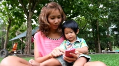 An asian boy and mother are playing funny game on smart phone at the park Stock Footage