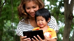 An asian boy and mother are playing funny game on tablet at the park Stock Footage