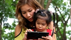 An asian girl and mother are playing funny game on tablet at the park Stock Footage