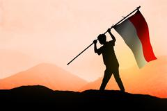 Successful silhouette man waving Indonesian flag on th mountain - stock photo