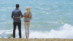 Attractive romantic couple kiss at the beach as they look out to sea.  Stock Footage
