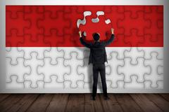 Business man assemble indonesian flag from jigsaw Stock Photos