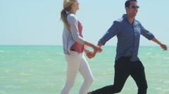 4K Attractive romantic couple running on the beach pause for a kiss - stock footage
