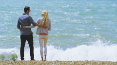 Attractive romantic couple kiss at the beach as they look out to sea.  - stock footage