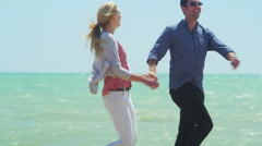 4K Attractive romantic couple running on the beach pause for a kiss Stock Footage