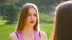 Two friends girls talking in park smiling sunny day ots, over the shoulder. - stock footage