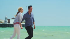 4K Attractive romantic couple holding hands as they walk along the beach Stock Footage