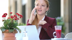 Attractive woman in the street restaurant talking on the phone and uses laptop. Stock Footage
