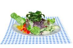 Salad plate on blue white table cloth - stock photo