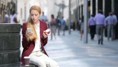 Healthy lunch business woman.A young woman eating a red apple on a city center. Stock Footage