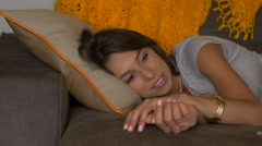 Attractive woman lying on couch watching TV sleepy -slider shot Stock Footage