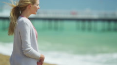 4K Portrait of beautiful woman standing alone at the beach. Stock Footage