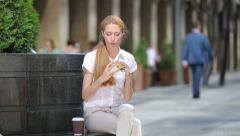 Quick lunch busy woman. A young woman eating a hamburger on a city street. Stock Footage