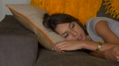 Attractive woman lying on couch using remote control -slider shot Stock Footage
