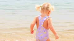 Little girl with hairtails backside walks in shallow seawater Stock Footage