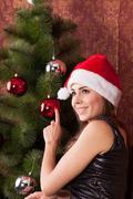 Woman decorate the Christmas tree Stock Photos