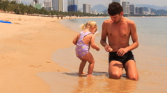 Father feeds little girl sitting on edge of seawater on beach Stock Footage