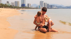 Father plays two little girls sitting on edge of sea on beach Stock Footage
