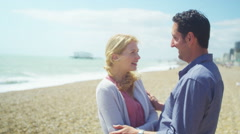 4K Portrait of romantic couple on beach, kiss & smile to camera.  - stock footage