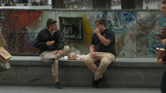 Two men sitting near the Fountain of International Friednship, Berlin Stock Footage