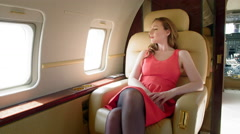 Attractive brunette in red dress relaxes and smiles on executive jet 4K Stock Footage