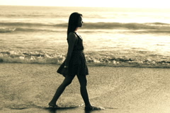 Silhouette of young woman walking through the vawes during sunset, 240fps NTSC Stock Footage