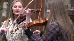 Young woman violin duo playing in the street . 4K Stock Footage