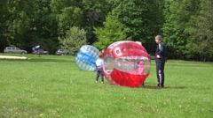 Kids with parents spent leisure with zorb balls bubbles in park. 4K Stock Footage