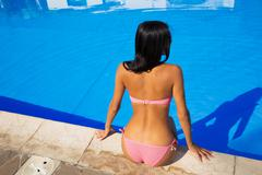 Woman in bikini sitting near swim poo Stock Photos