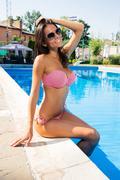 Smiling woman sitting in bikini near swim pool - stock photo