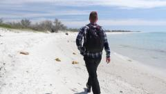 Traveler walks along empty island sand beach in search of adventure Stock Footage