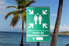 Evacuation assembly point sign under blue sky and paradise seascape Stock Photos