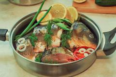 Fish and components for her preparation in a large skillet. - stock photo