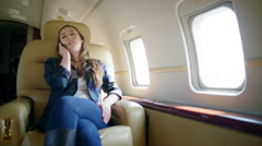 Attractive brunette using cellphone in comfortable seat on private jet 4K Stock Footage