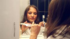 Young pretty woman brushing teeth in front of the mirror Stock Footage