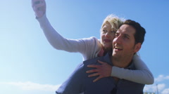 4K Happy fun couple playing piggyback pause to take a selfie on mobile phone - stock footage
