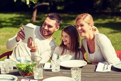 Happy family with tablet pc at table in garden Stock Photos
