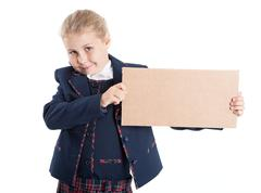 Smiling schoolgirl showing empty paperboard in hands, isolated on white - stock photo