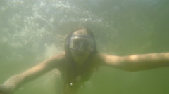 Beautiful slim woman in  swimming mask dives into water and swim under water. Stock Footage