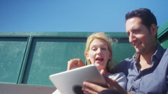 4K Happy romantic couple with computer tablet, relaxing on bench at the seaside Stock Footage